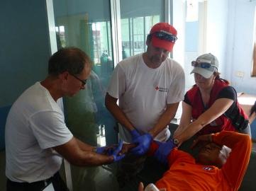 Les membres de l'ERU de soins de santé de base et de soins chirurgicaux de la Fédération internationale s'entraident pour soigner le bras fracturé de Rogelio Arges. M. Arges est le premier patient soigné par le personnel de l'hôpital de campagne de la Croix-Rouge, le jour précédant l'ouverture officielle de l'établissement. M. Arges s'est fracturé le bras en trébuchant alors qu'il s'affairait à déblayer des débris dans la ville d'Ormoc, sévèrement touchée par le typhon. Des membres de la Croix-Rouge canadienne et de la Croix-Rouge de Norvège se sont chargés de soigner sa fracture.