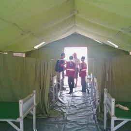 Des bénévoles en gestion des sinistres de la Croix-Rouge philippine en pleine discussion avec Sébastien Jouffroy, chef de l'ERU, dans la tente du service de maternité nouvellement érigée.