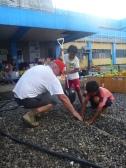 Des frères et des sœurs des patients admis en pédiatrie aident le technicien en chef à creuser une tranchée étroite pendant la mise en place de l'ERU de soins de santé de base et de soins chirurgicaux de la Fédération internationale à Ormoc, aux Philippines