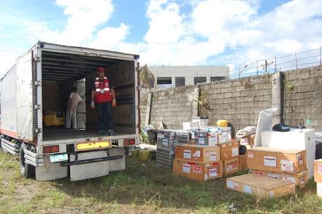 Un membre de l'équipe d'intervention lors de catastrophes de la Croix-Rouge philippine aide à décharger la cargaison d'un camion transportant de l'équipement médical de base ainsi que de l'équipement chirurgical destiné à l'ERU déployée à Ormoc, dans la province de Leyte.