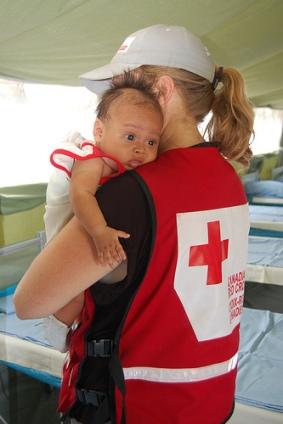 L'infirmière en chef Dawn Anderson tient dans ses bras le premier patient de l'ERU de soins de santé de base et de soins chirurgicaux de la Fédération internationale : le petit Raymart Recart, âgé de 3 mois.
