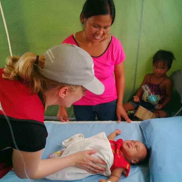 L'infirmière en chef visite les premiers patients de l'hôpital, Raymart, trois mois, sa maman Marie-Anne et sa sœur Risa.  Leur maison a été complètement détruite par le typhon Haiyan.